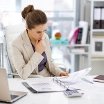 Thoughtful business woman documents in office